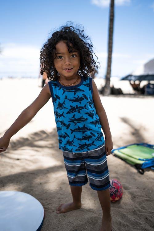Smiling Hispanic boy standing on sandy seashore