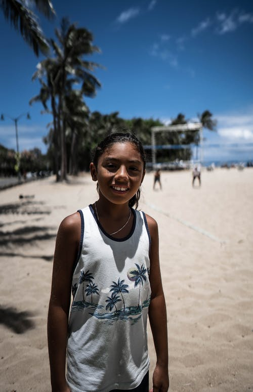 Positive African American girl in white shirt standing on sandy tropical beach with palms and looking at camera happily