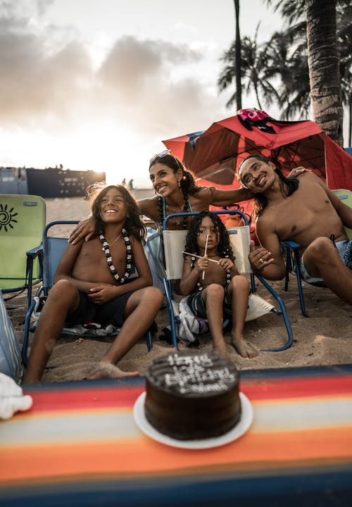 Happy Hispanic family embracing and chilling on sunny beach