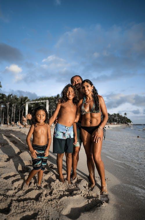 Joyful Hispanic family standing on sandy tropical beach
