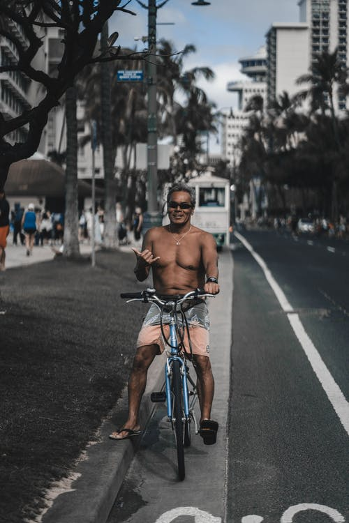 Cheerful ethnic man sitting on bicycle with shaka sign