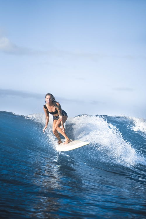 Full length concentrated fit female surfer crouching on surfboard and splashing blue seawater on sunny weather