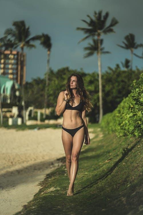 Full length graceful fit female wearing black bikini walking on tropical sunny beach and looking away