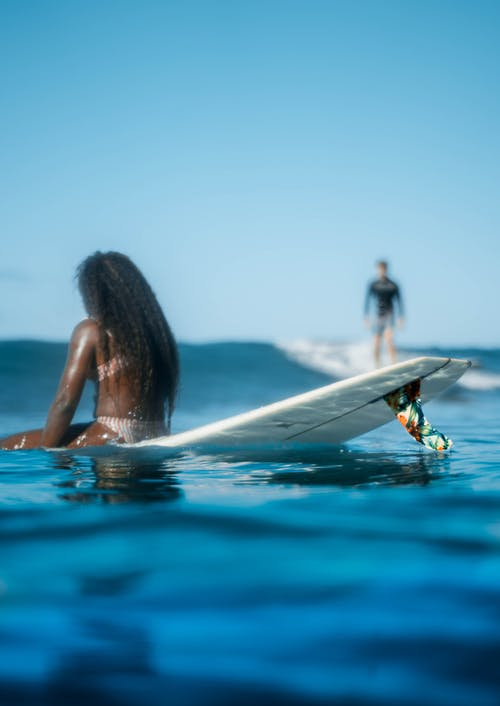 Back view anonymous African American female resting on surfboard on azure seawater near blurred surfer