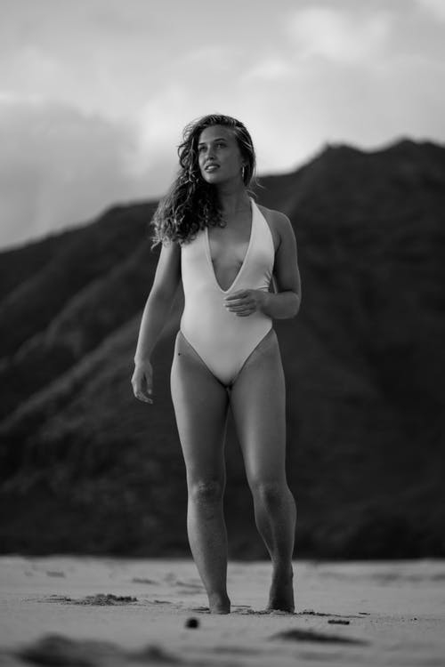 Black and white of happy fit young female tourist with long wavy hair in swimsuit relaxing on sandy beach and looking away