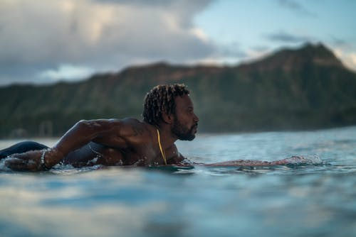Sporty young black man swimming in ocean lying on surfboard