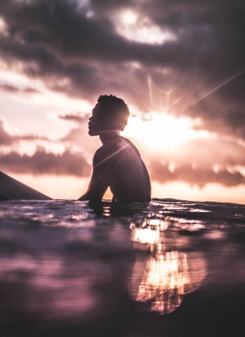 日没時に海の水でリラックスしている認識できない黒人男性