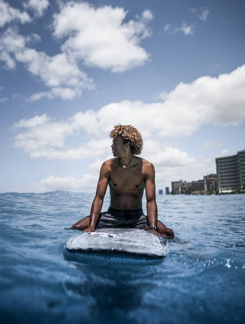 Shirtless young black male athlete with Afro hair sitting on surfboard in rippling sea and looking away