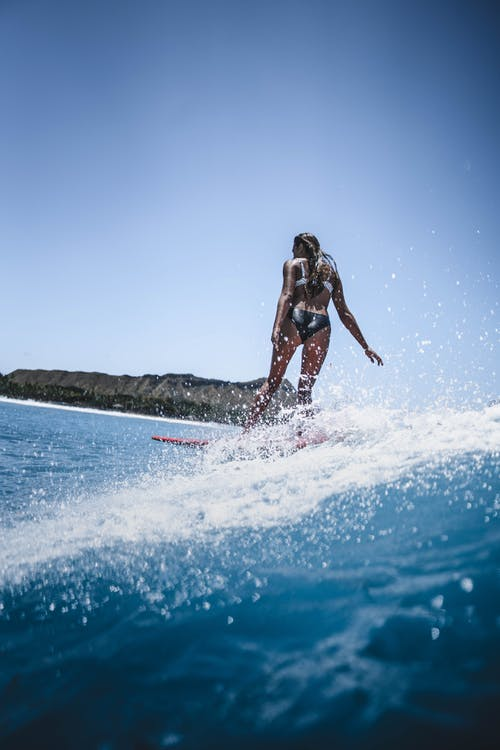 Active fit woman surfing in ocean on sunny day