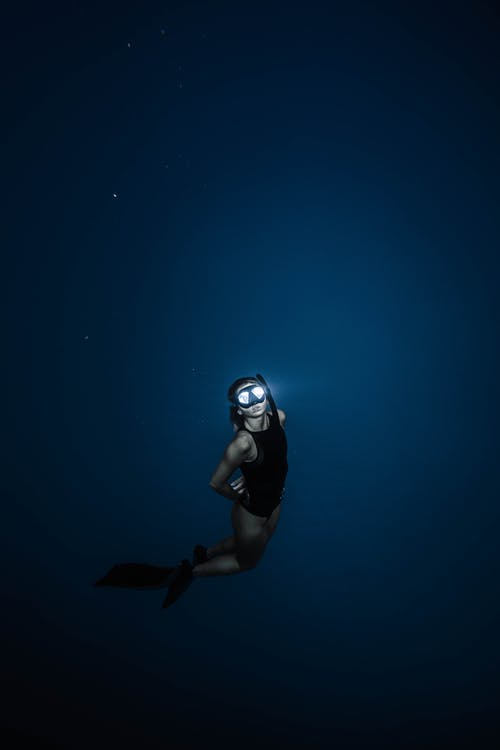 Unrecognizable woman diving in blue sea water