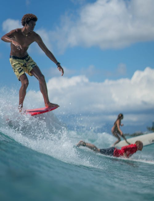 Muscular ethnic sportsman riding wave on surfboard on sunny day
