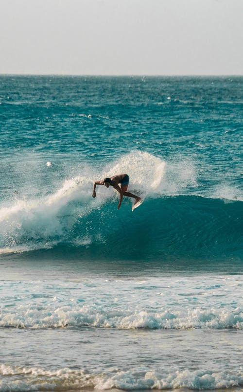 Anonymous sportsman doing extreme trick on surfboard in sea