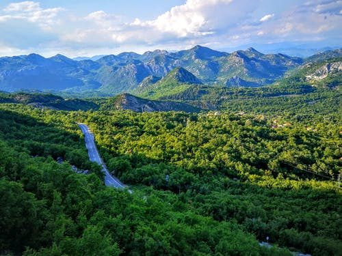 Spectacular landscape of empty asphalt road surrounded by lush green forest in amazing  mountainous valley on sunny day