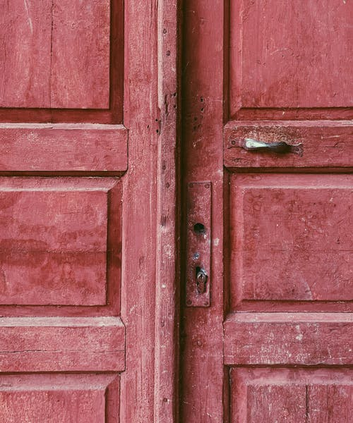 Shabby wooden red door of aged building