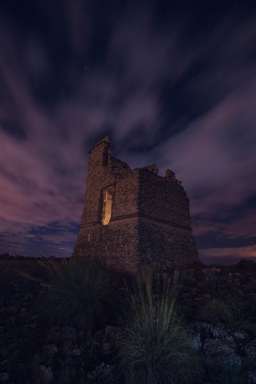 Ruined medieval castle against purple night sky