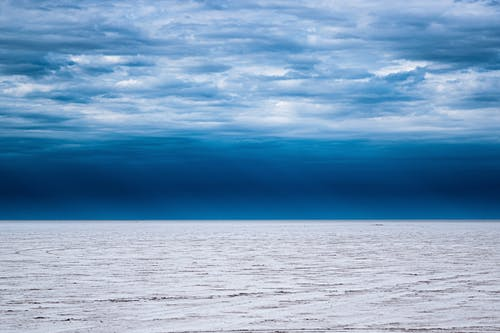 Picturesque scenery of clouds floating in blue sky over wavy powerful sea in evening