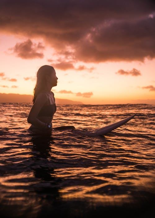 Photo Of Woman Riding Surfboard