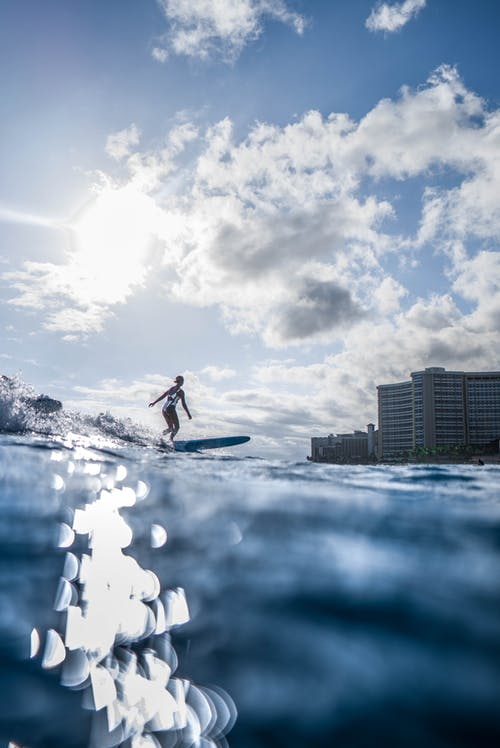 Photo Of Person Riding Surfboard