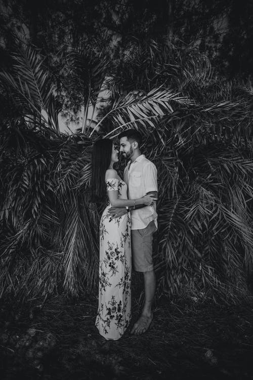 Monochrome Photo Of Couple Standing Beside Plant