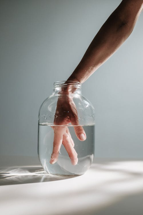 Hand Of A Person Inside A Clear Glass Jar With Water