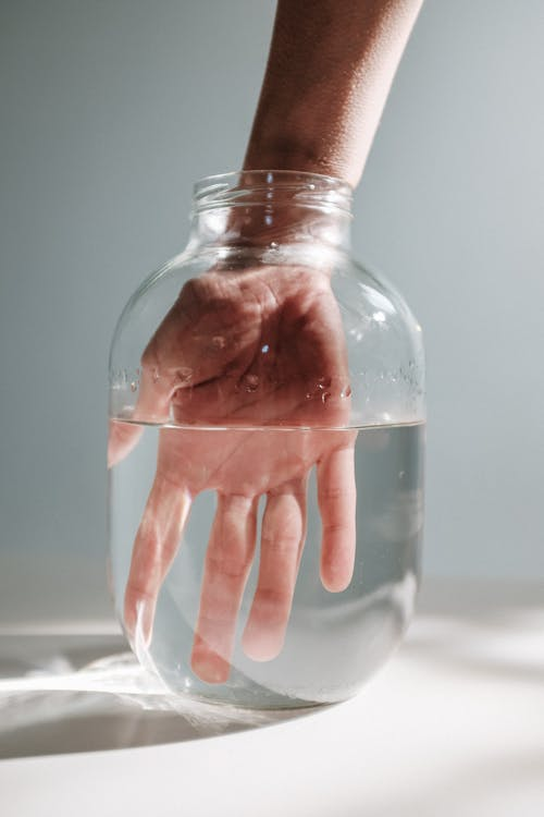 Photo Of Person's Hand Submerged On A Jar With Water