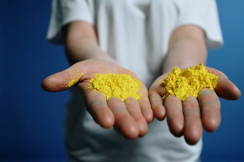 Photo Of Yellow Powder On Person's Hand