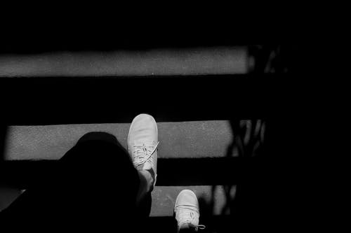 Person Wearing White Sneakers Walking On Stairs