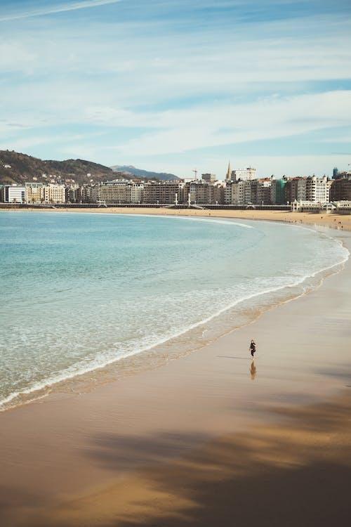 Photo Of Person Walking Beside Beach