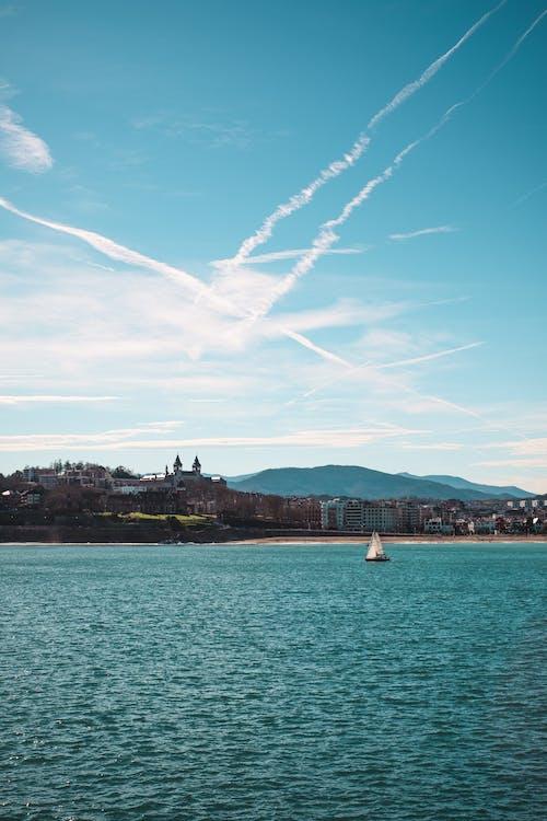 White Sailing Boat on Sea Under Blue Sky