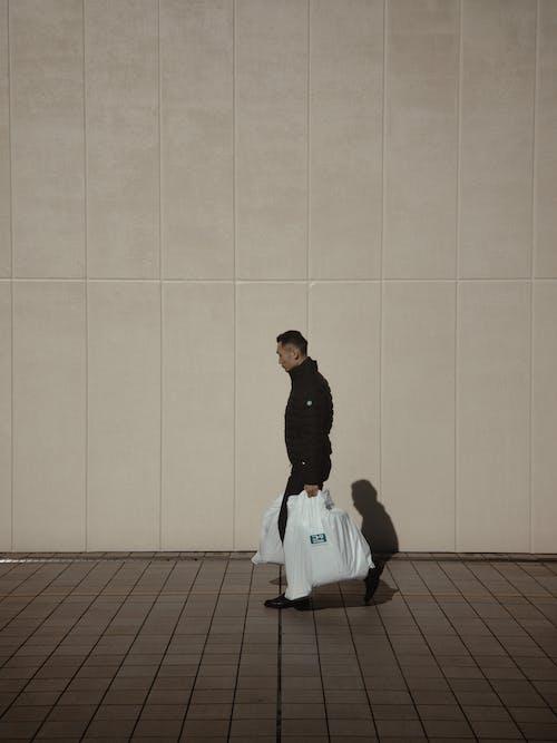 Man Walking On Sidewalk Carrying Shopping Bags