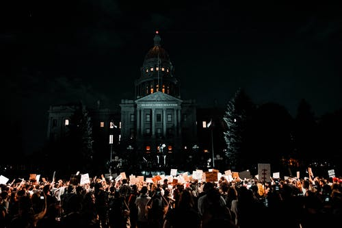 People Rallying in Front of White Building during Nightime