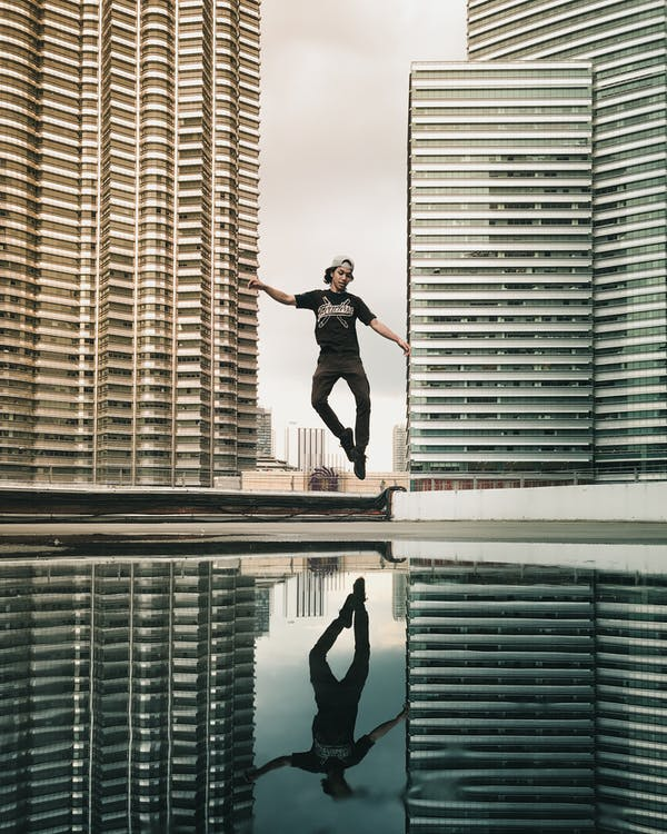 Full body of young ethnic male in casual outfit jumping on street between modern skyscrapers against cloudy sky