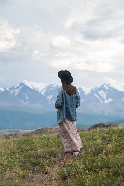 Woman Denim Jacket Standing on Green Grass Field
