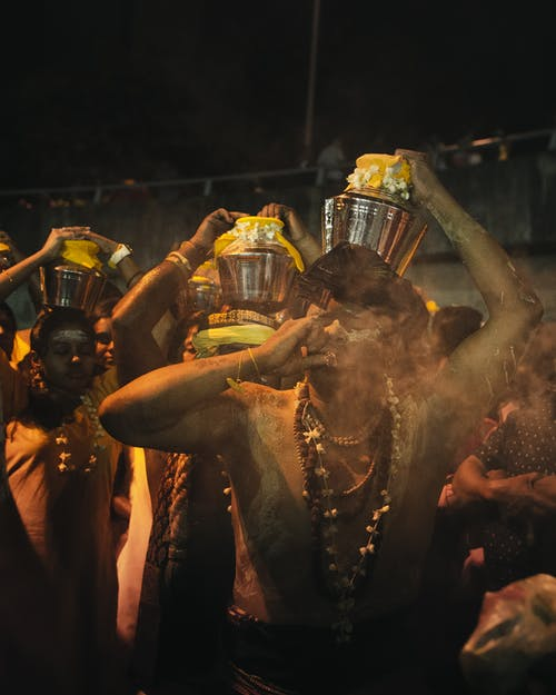 Anonymous ethnic Hindu people carrying pots of milk on head during traditional religious festival at night
