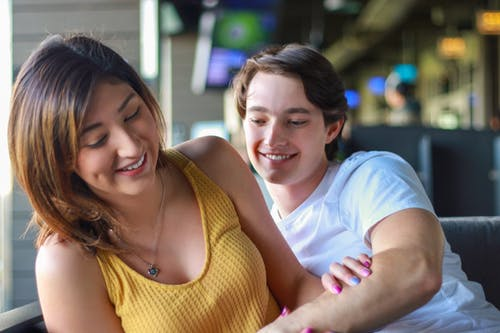 Happy young diverse couple hugging and smiling in cafeteria