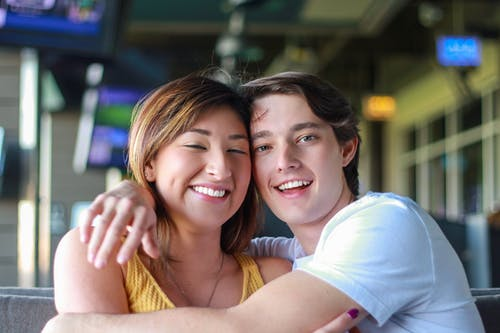 Happy young multiracial couple hugging while resting in cafe
