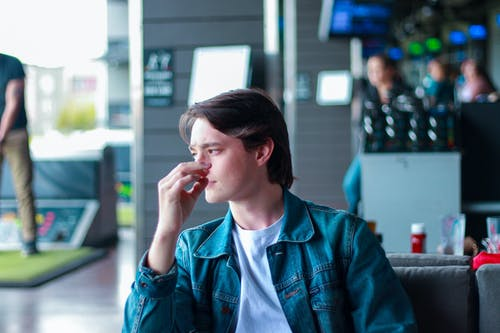 Thoughtful young male chilling in modern cafe in daytime