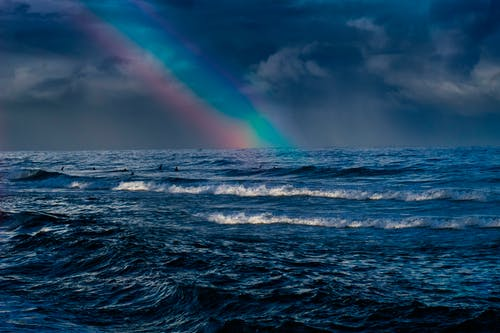 Ocean Waves Under Rainbow and Cloudy Sky