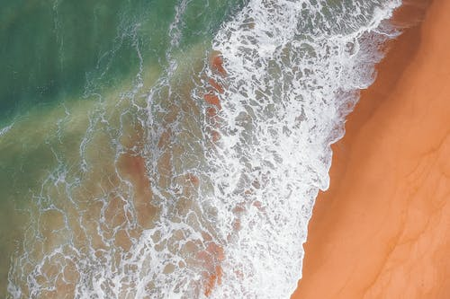 Aerial view of foamy sea waves turquoise color running up coast with golden sand