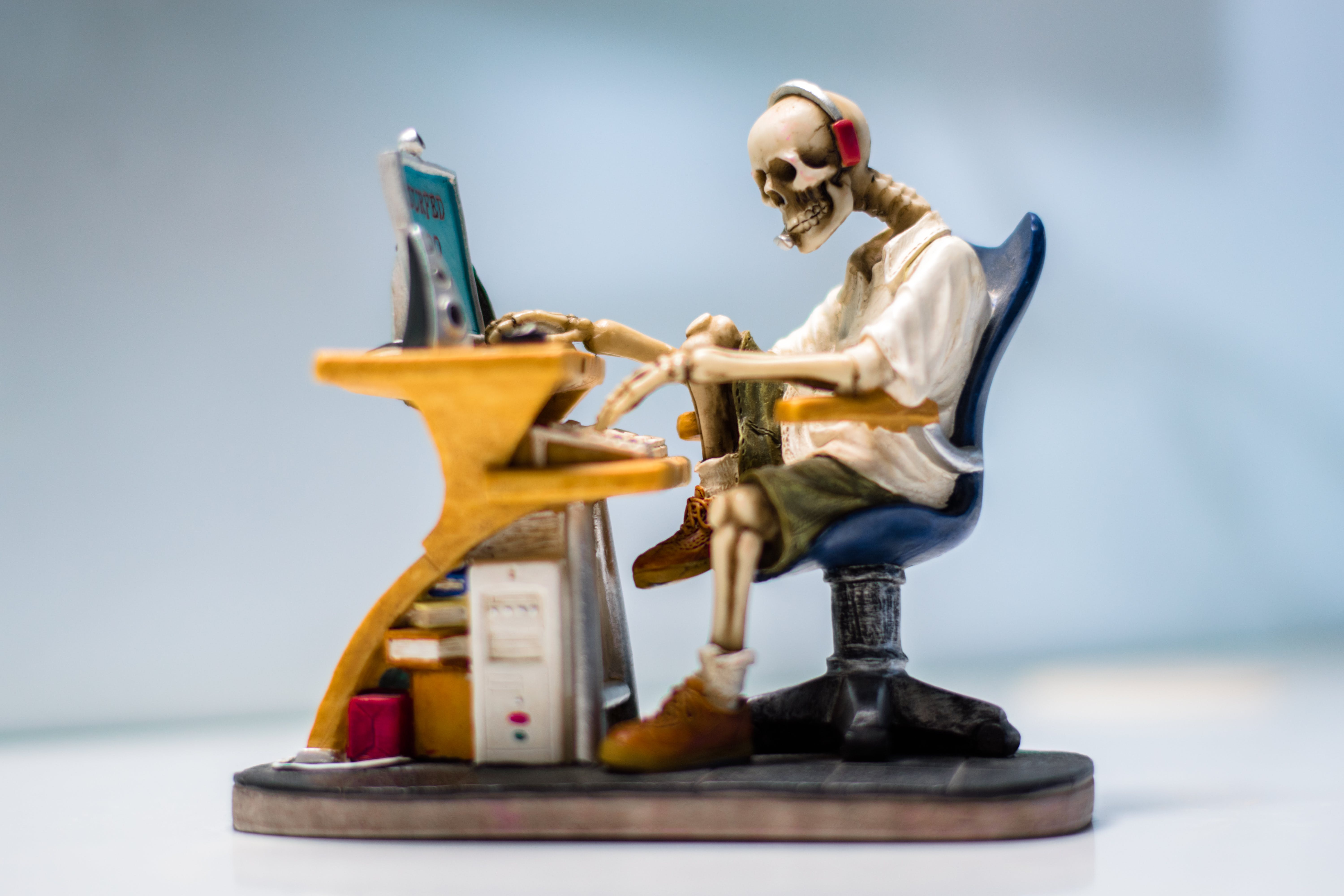 Figurine of Human Skeleton Sitting Infront of Computer