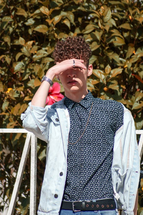 Young confident man with curly hair wearing trendy clothes covering eyes from sunlight while standing against lush greenery