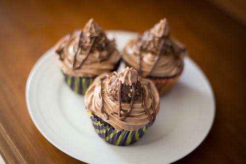 Sweet chocolate cupcakes with cream on plate