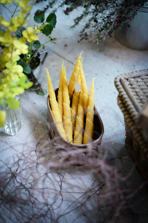 From above of arranged beeswax candles in container placed near glass vase with plant branches and basket