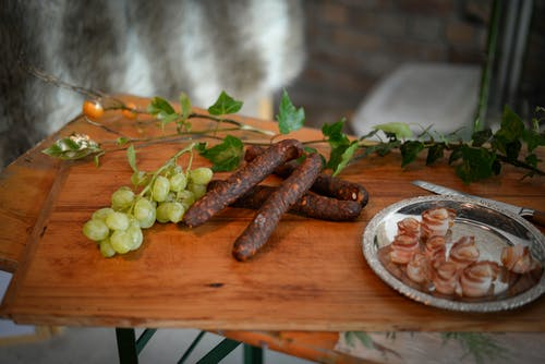 From above of appetizing sausages placed near branch of grapes and bacon plate on wooden board