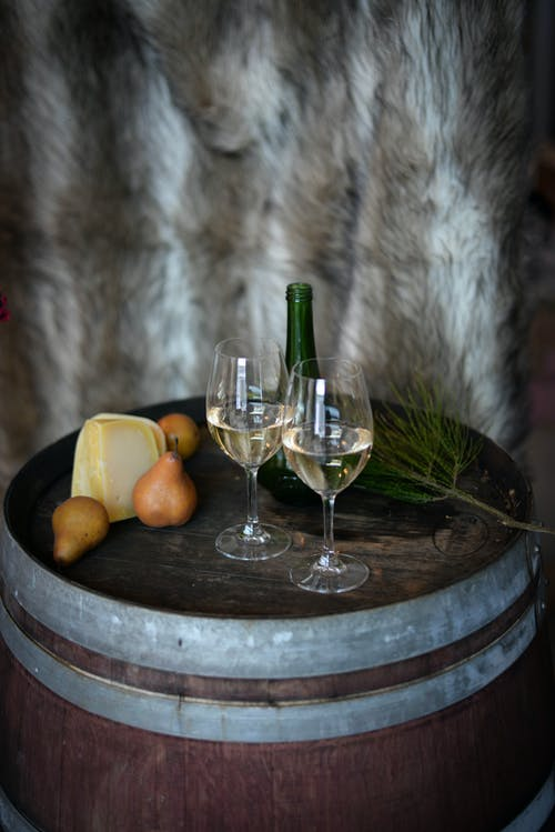 From above of composed glasses with alcoholic drink placed on wooden barrel near  cheese and pears