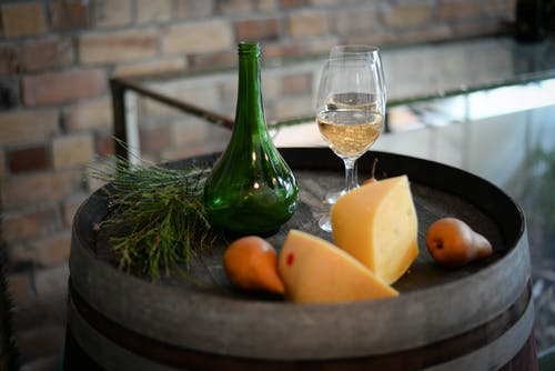 High angle of glass bottle with wineglasses placed on barrel with aromatic cheese and pears