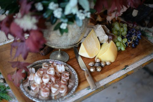 From above of served wooden board with bacon plate cheese and grapes near knife and bunch of flowers