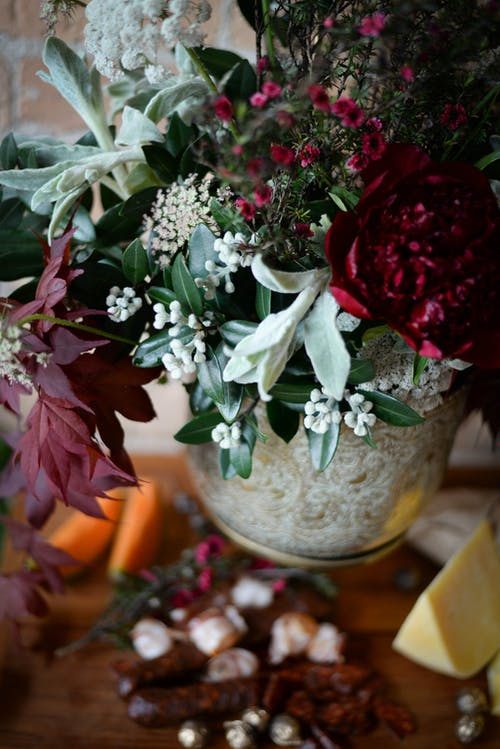 High angle of bunch of fresh flowers placed near meat products and cheese in rustic style