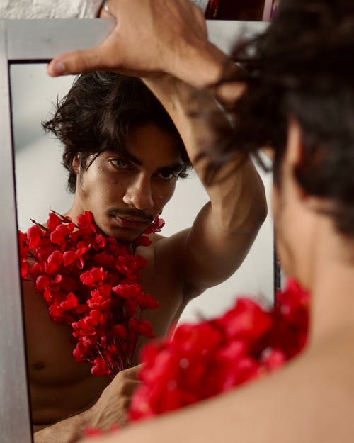 Ethnic man with bright bunch of flowers looking at reflection
