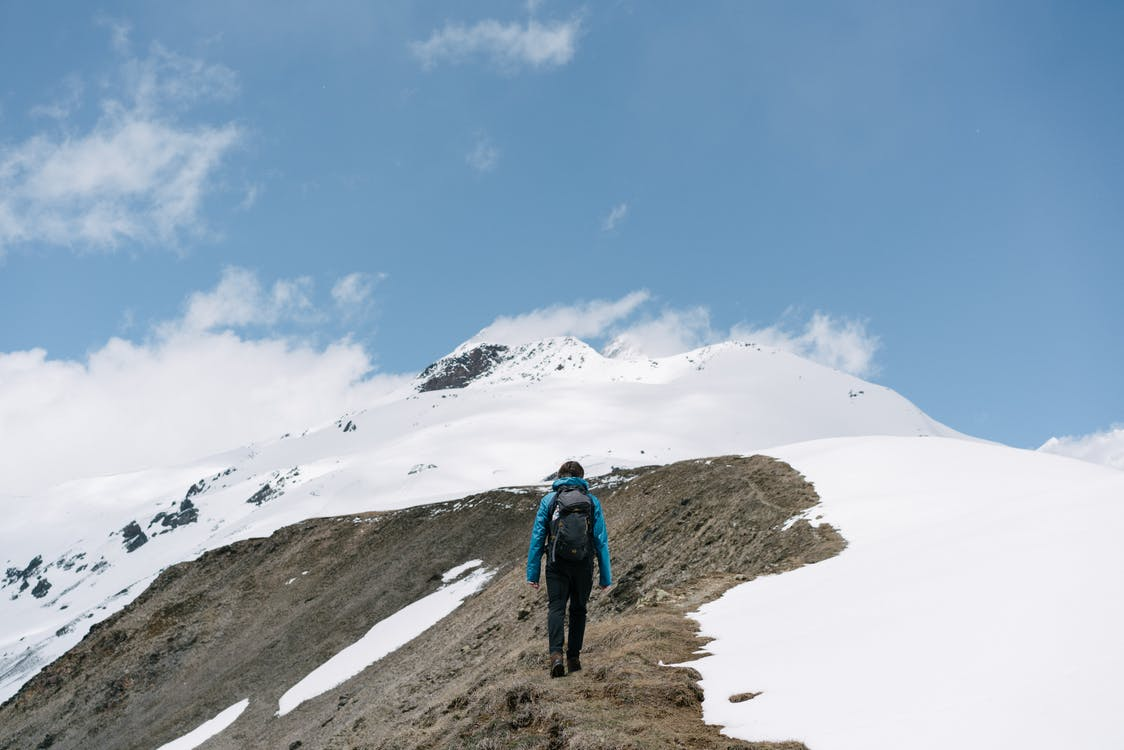 Person in Blue Jacket and Brown Pants Walking on Snow Covered Ground Under Blue Sky during